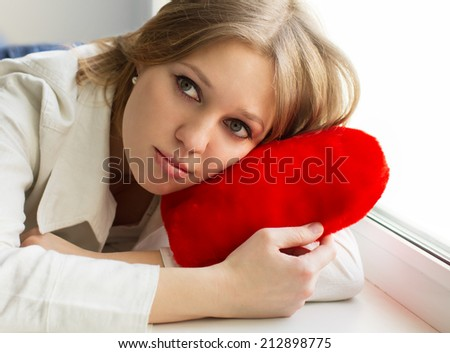 Beautiful girl is sad, sadness due the guy, keep heart sit near the window - stock photo