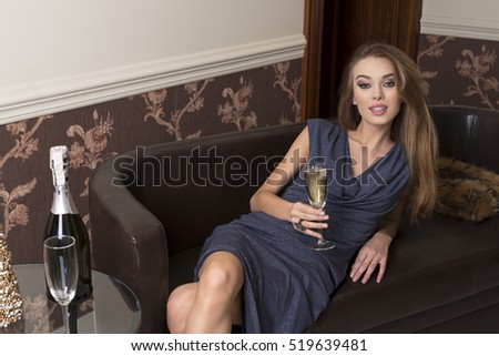 beautiful girl is sitting in elegant ambient on sofa, taking a flute of champagne in the hand and looking in camera with happy expression
