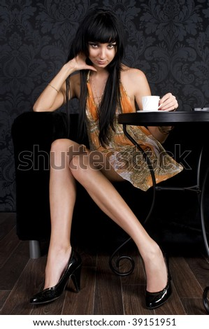 Beautiful girl is sitting in the cafe and  drinking coffe - stock photo