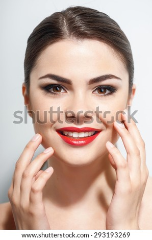 Beautiful girl is smiling and happily touching her cheeks. She has Caucasian appearance and red lips. Isolated on grey background - stock photo