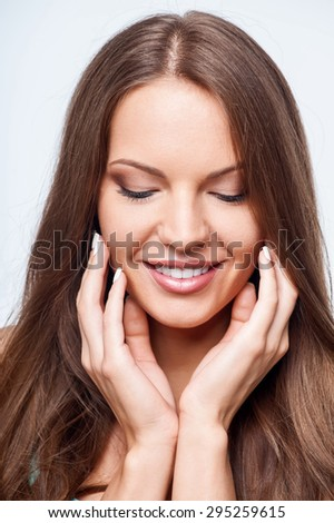Beautiful girl is smiling happily. She is looking down and touching her face with both her hands. Isolated on background - stock photo