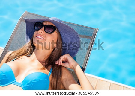 Beautiful girl is sunbathing in swimwear with pleasure. She is lying near a swimming pool. The lady closed her eyes with enjoyment and smiling. She is wearing sunglasses and a hat - stock photo