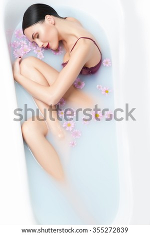 Beautiful girl is taking a bath and relaxing. She closed her eyes with pleasure. The lady is lying with pretty smile - stock photo