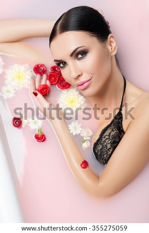 Beautiful girl is taking a bath with flowers. She is lying and smiling. The lady is touching rose and looking at camera with passion - stock photo