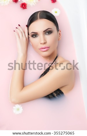 Beautiful girl is taking a bath with pleasure. She is lying in water with flowers and looking forward with desire - stock photo