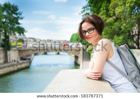 Beautiful girl is walking around the city and admire good location near the river in Paris, France