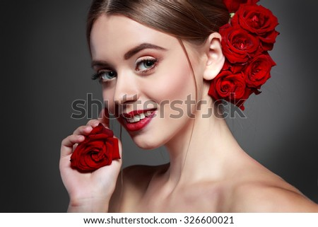 Beautiful girl, isolated on a dark - grey background with red flowers in hairs, emotions, cosmetics - stock photo