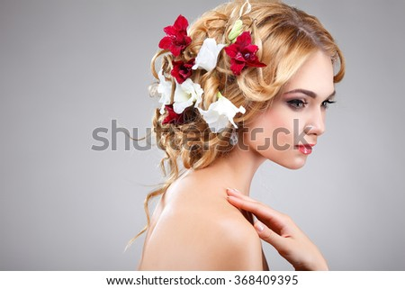 Beautiful girl, isolated on a light - grey background with varicoloured flowers in hairs, emotions, cosmetics - stock photo