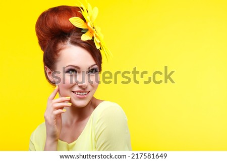 Beautiful girl, isolated on a yellow background with yellow flower in hairs, emotions, cosmetics - stock photo