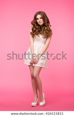 Beautiful girl isolated on pink background. Standing, looking at camera. White dress and white shoes. Beautiful hairstyle and makeup.