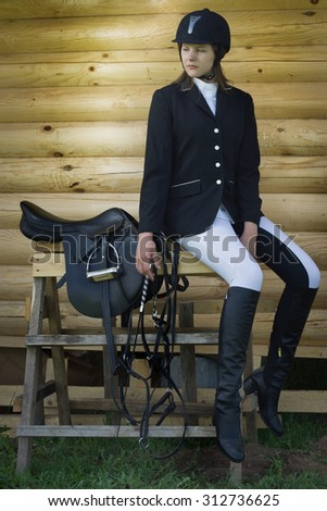 Beautiful girl jockey dressing uniform posing outdoors - stock photo