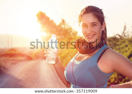 Beautiful girl jogger outdoors drinking water at sunset - stock photo