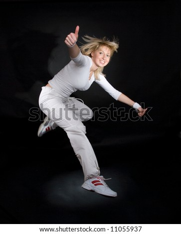 Beautiful girl jumping in studio. Note that girl is not isolated and image has special light effects.