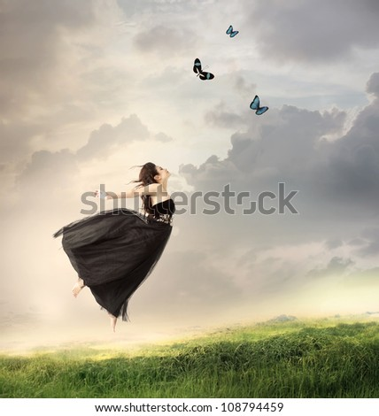 Beautiful Girl Jumping in the Air on a Mountain