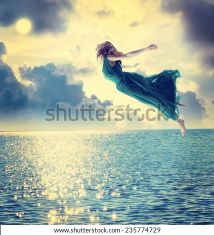 Beautiful girl jumping into the blue night sky over the ocean - stock photo