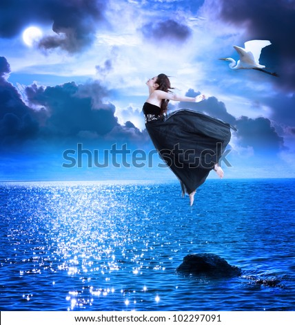 Beautiful girl jumping into the blue night sky with white egret - stock photo