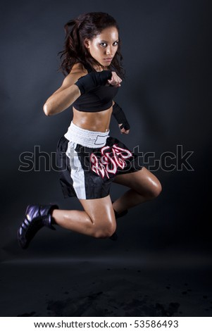Beautiful girl jumping to fight on black background - stock photo