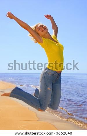 Beautiful girl jumps on a beach - stock photo