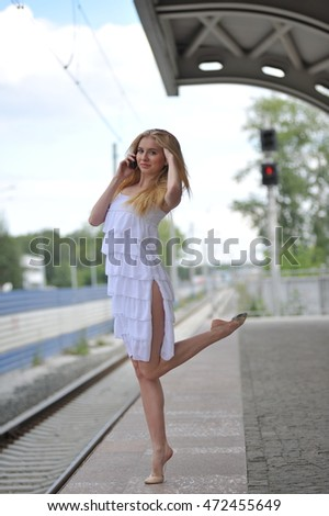 Beautiful girl jumps on the train station