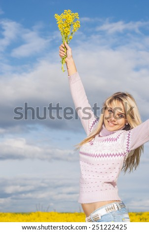 Beautiful girl laughs and lifts a bouquet with yellow florets - stock photo