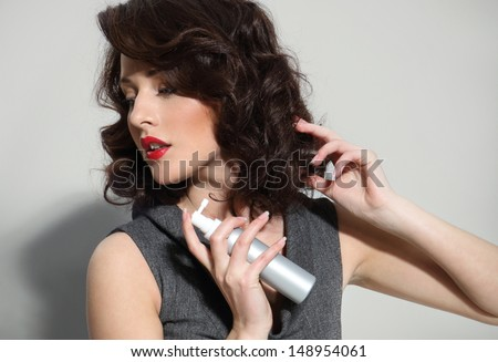 Beautiful girl laying fixes using hairspray - stock photo