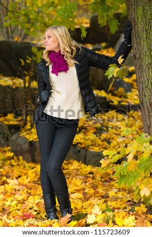 Beautiful girl leans on tree, several leaves on the ground - stock photo