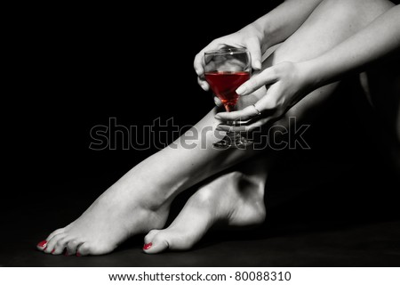 Beautiful girl legs and a glass of alcoholic beverage, black white photo (red wine in glass) - stock photo