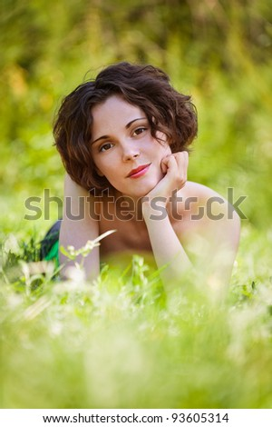 Beautiful girl lies on lawn. - stock photo