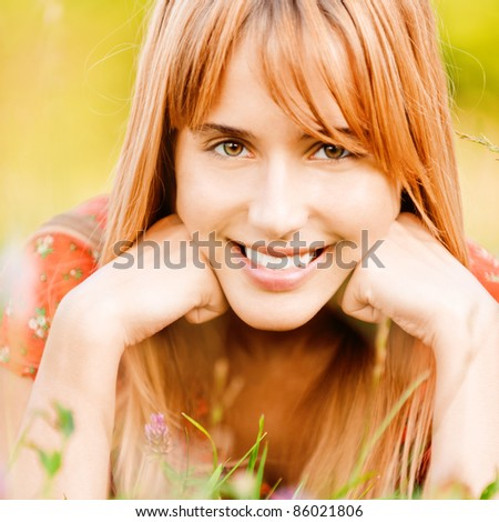 Beautiful girl lies on lawn on which clover grows. - stock photo