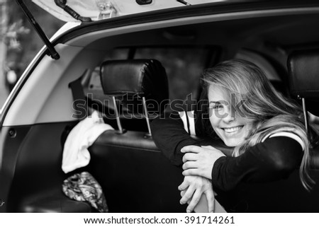 beautiful girl , like a cheerleader . Attractive girl sitting in a car and smiling . pretty girl traveling in a car with friends. - stock photo