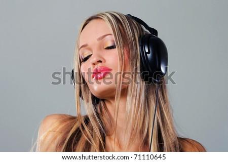 Beautiful girl listening music in big headphones - stock photo