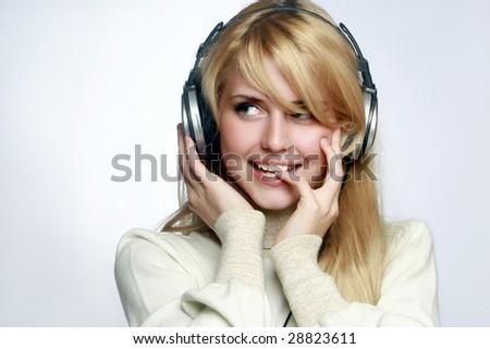 Beautiful girl listening music in headphones. - stock photo