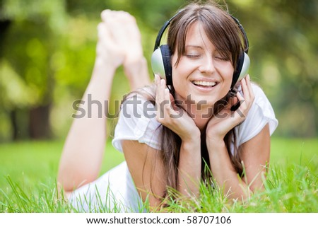 Beautiful girl listening music in the park - stock photo