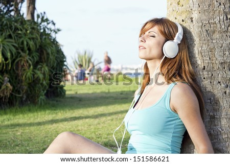 beautiful girl listening music on grass in really good day - stock photo