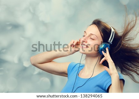 Beautiful girl listening to music on headphones - stock photo