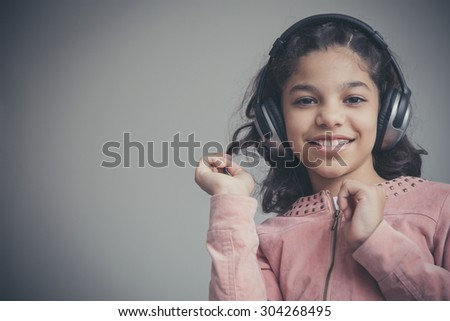 Beautiful girl listening to music on her headphones and happy.  Photo taken on: August 01st, 2015