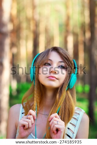 Beautiful girl listening to music with headphones at the park - stock photo