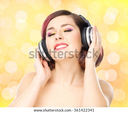 Beautiful girl listening to the music throughout headphones on bubble background. - stock photo