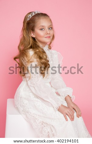 beautiful girl little princess long hair, curly and amazing blue eyes in communion dress and tiara on his head, sitting in elegant palatial room with a dressing table with mirror in the background