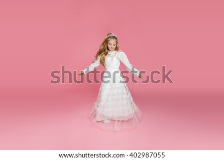 beautiful girl little princess long hair, curly and amazing blue eyes in communion dress and tiara on his head, sitting in elegant palatial room with a dressing table with mirror in the background - stock photo