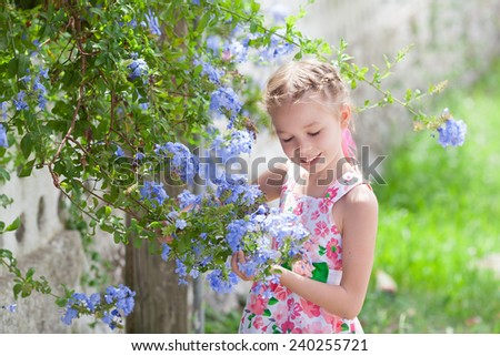 Beautiful girl looking at blue flowers - stock photo