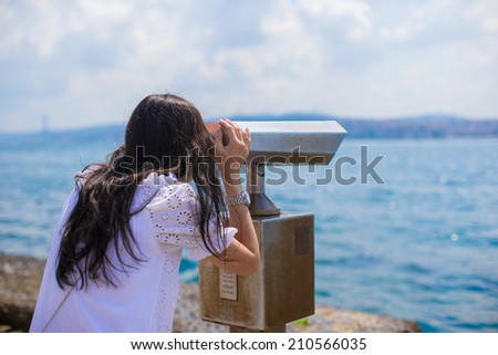 Beautiful girl looking at coin operated binocular on the Bosphorus Strait - stock photo