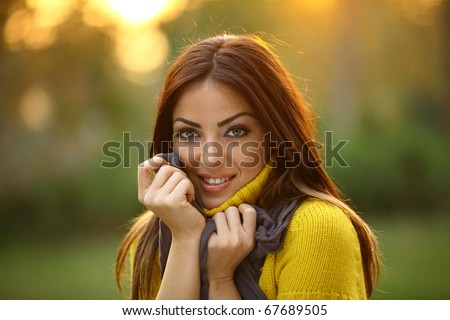 Beautiful Girl looking at the camera holding her scarf - stock photo