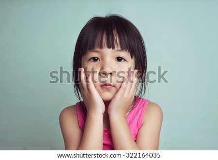 Beautiful girl looking sad with pouted lips. Closeup portrait of cute asian kid . - stock photo