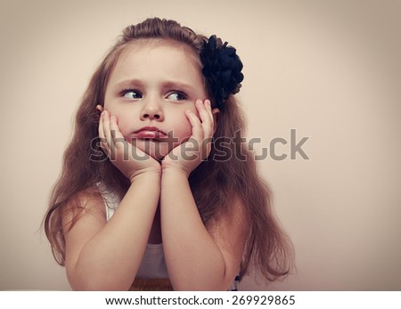 Beautiful girl looking sad with pouted lips. Closeup portrait of cute kid with long hair. Vintage - stock photo