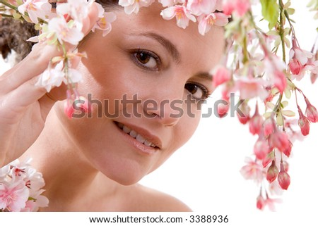 Beautiful girl looking through an overhanging blossom branch - stock photo