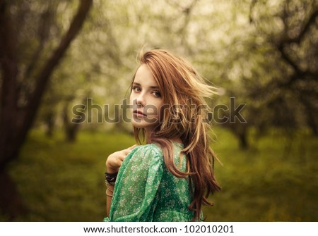 beautiful girl looks in the garden - stock photo