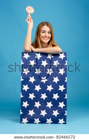 Beautiful girl looks out from a big bag - stock photo