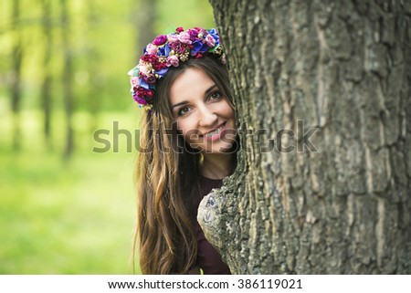 Beautiful girl looks out from behind a tree - stock photo