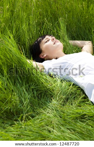 beautiful girl lying down of grass. Copy space - stock photo